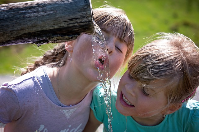 dwie dziewczynki piją wodę bezpośrednio z poidełka.
