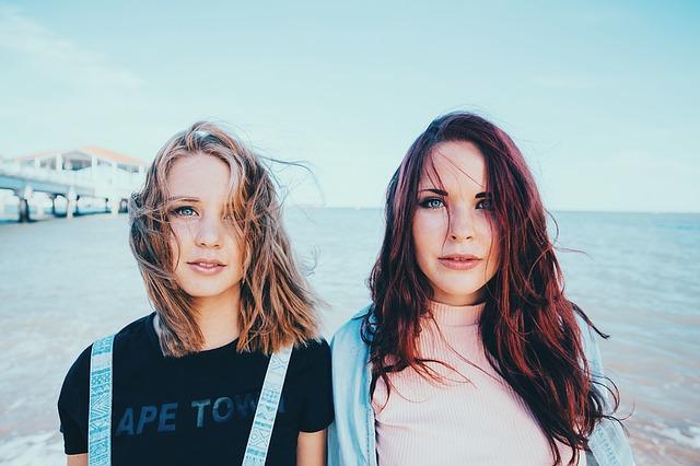 dwie młode dziewczyny ba tle mola i morza