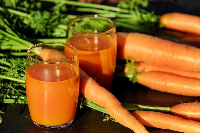 domowy sok z marchwi w szklankach w towarzystwie warzyk