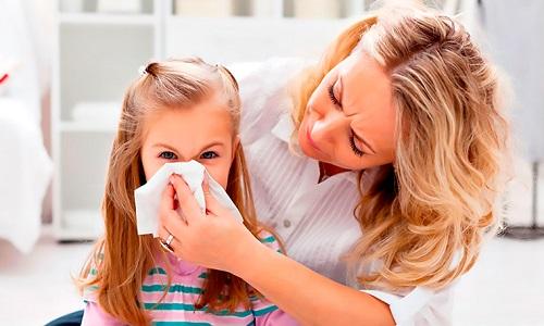 mama pomaga małej dziewczynce wydmuchać nos