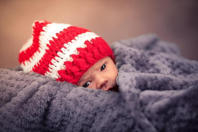 biegunka u niemowlaka otulonego w mięciutki kocyk w kolorze gołębim i czerwono białej czapeczce
