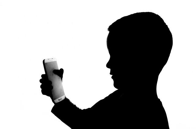 na karte doładowanie, dziecko trzyma w ręku smartfona