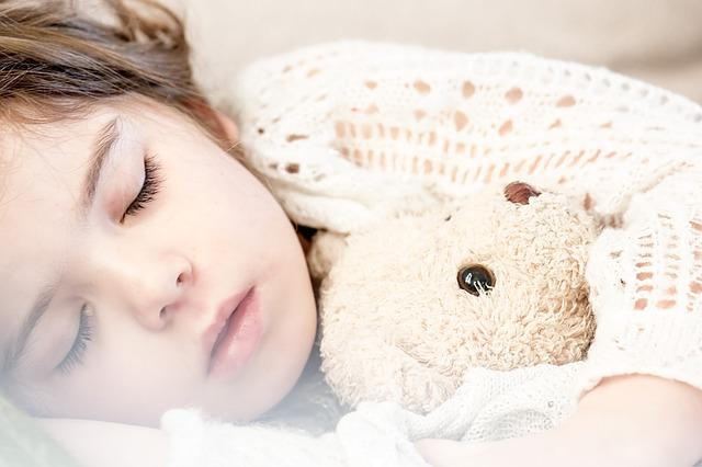 syrop na przeziębienie dzieci - mała chora dziewczynka śpi wtulona w ukochanego misia